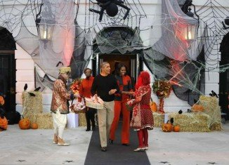 Barack Obama and first lady Michelle Obama, clad in orange and black, emerged in the evening to greet the zombies, wizards and superheroes