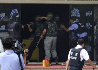 Two police officers and nine axe-wielding assailants have been shot dead during an attack on a police station in China's volatile western Xinjiang province
