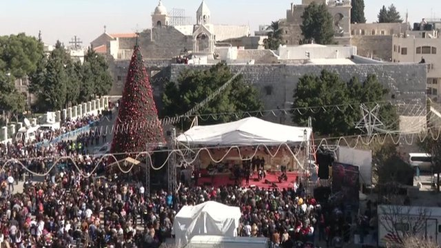 Crowds of pilgrims and tourists have begun to gather in the biblical town of Bethlehem to kick off Christmas Eve celebrations photo