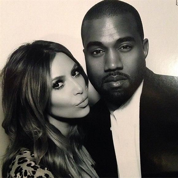 "Kim Kardashian and Kanye West inside the ""Naughty or Nice"" photo booth"