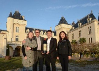 Lam Kok and James Gregoire pictured with their wives while celebrating the sale of the chateau