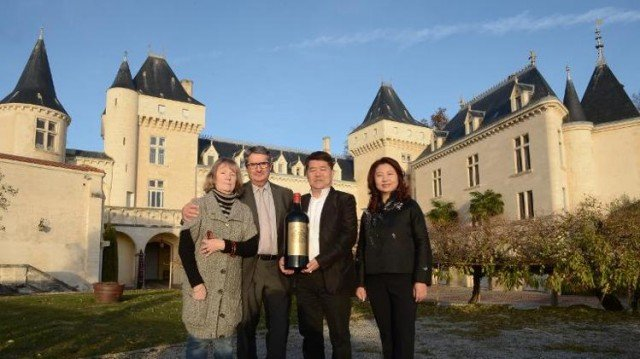 Lam Kok and James Gregoire pictured with their wives while celebrating the sale of the chateau  640x359 photo