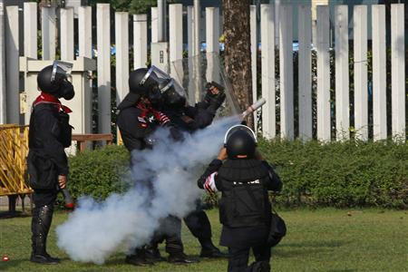 Thai riot police have fired teargas at protesters trying to prevent political parties from registering for February's elections