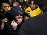 Justin Bieber handed himself in at a Toronto police station where he was mobbed by TV crews, news photographers and screaming teenage fans