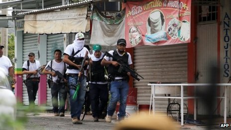 Mexican federal troops will take over security in Michoacán where vigilante groups and a drugs cartel are clashing photo