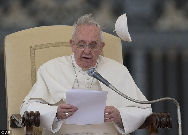 A gust of wind blows away Pope Francis' skull cap, or zuchetto, as he delivers his message during his weekly general audience in St. Peter's Square at the Vatican