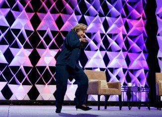 A woman was taken into custody after throwing what she said was a shoe at Hillary Clinton during a Las Vegas speech