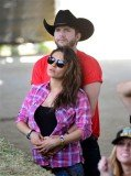 Mila Kunis showed off her baby bump as she attended the Stagecoach Music Festival in Indio, California, with Ashton Kutcher