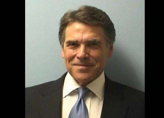 Showing no hint of worry on his face, Rick Perry flashed a thin, confident grin beneath perfect hair in his mug shot