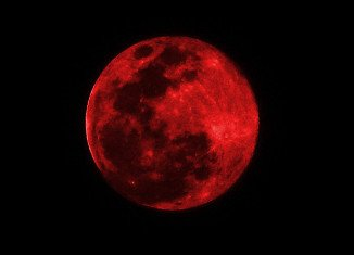 The Moon appears orange or red, the result of sunlight scattering off our atmosphere, hence the name Blood Moon